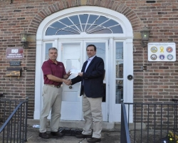 Dr. Bryan Cole, director of EKU's Department of Veterans Affairs, left, accepts a check from Ron Hink, BPBG project manager.